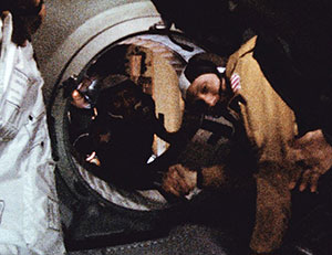 Apollo astronaut and Soyuz cosmonaut shake hands in space