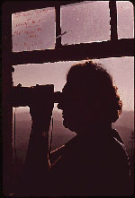 Photo of a woman looking through a telescope
